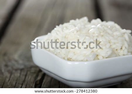 Bowl full of rice over wooden background - stock photo