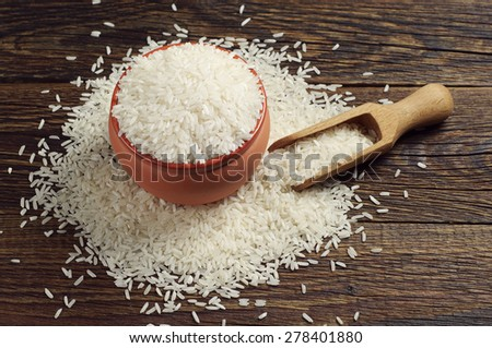Bowl full of white rice and scoop on dark wooden table - stock photo