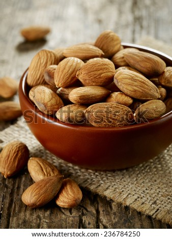 bowl of almond nuts on old wooden table - stock photo