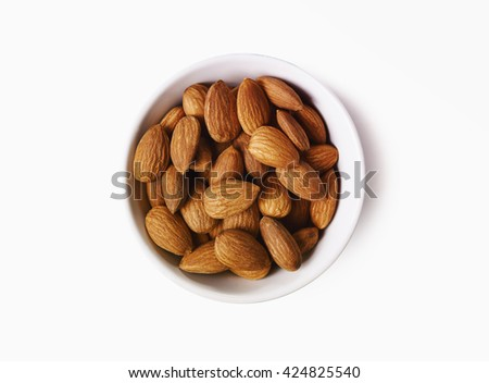 bowl of almond seeds isolated on white background. top view