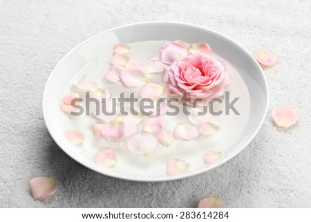 Bowl of aroma spa water with rose petals on towel, closeup - stock photo