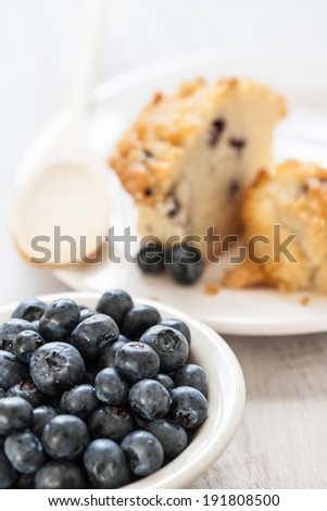 Bowl of blueberries with blueberry muffin breakfast with wooden spoon - stock photo