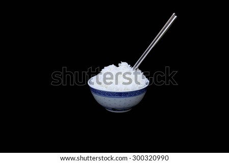 Bowl of boiled rice with silver chopsticks isolated in black background - stock photo
