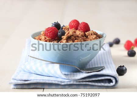 Bowl of breakfast healthy muesli with raspberry and blueberries - stock photo
