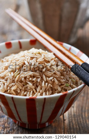 Bowl of brown rice with chopsticks - stock photo