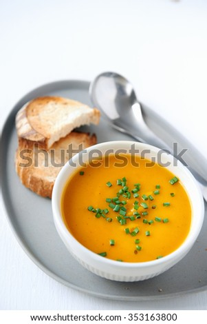 Bowl of butternut soup garnished with chives, served with toasted baguette bread slices  - stock photo