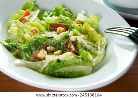 Bowl of Caesar salad with a fork - stock photo