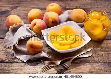 bowl of canned peaches with fresh fruits on wooden table