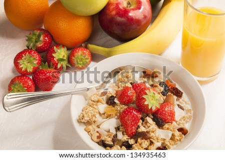 Bowl of cereal and fruits on tabletop - breakfast.