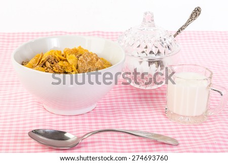 Bowl of cereal in brightly lit breakfast scene; cream and antique crystal sugar bowl with vintage sugar spoon on pink gingham table against white background. - stock photo