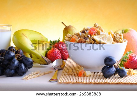 Bowl of cereal with fruit on a white wooden table and fresh fruits behind front view - stock photo