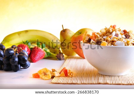 Bowl of cereal with fruit on a white wooden table and fresh fruits behind overview - stock photo