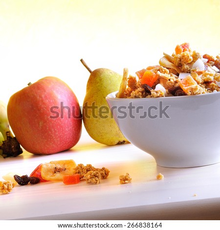 Bowl of cereal with fruit on a white wooden table and fresh fruits behind. Yellow gradient background with diagonal composition - stock photo
