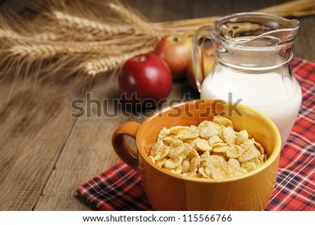 Bowl of cereals and the glass of milk on the wooden table
