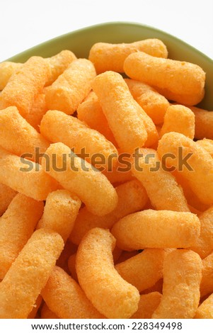 Bowl of cheese flavored puffed corn snacks - stock photo