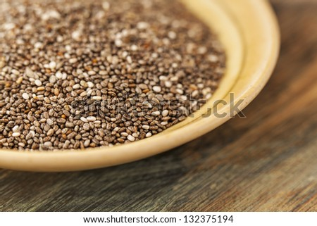bowl of chia seeds on wood surface - a close-up with a shallow depth of field - stock photo