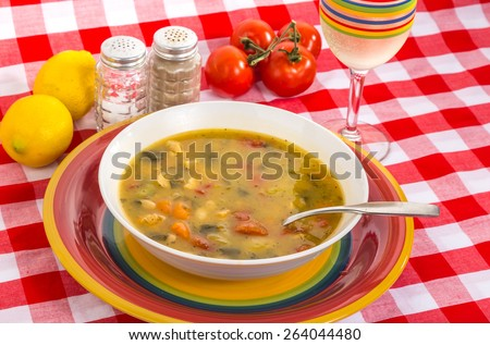 Bowl of Chicken Soup, Tuscany Style, in colorful surroundings and Italian style tablecloth.  Stemmed glass of White Riesling Wine.  Glass matches plate. - stock photo