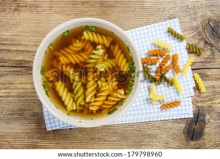 Bowl of chicken soup with noodle on wooden table - stock photo