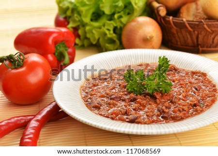 Bowl of chili with peppers,  beans and  basket of bun