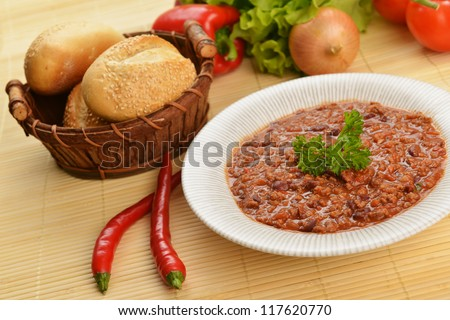 Bowl of chili with peppers,  beans and  basket of bun - stock photo