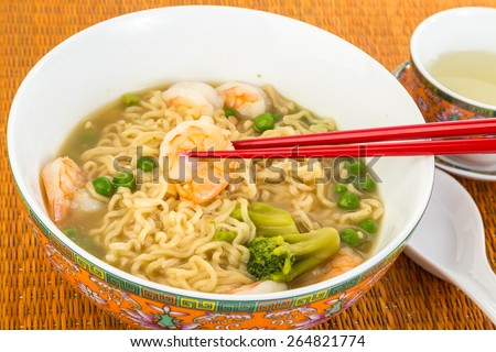 Bowl of Chinese Noodle Soup with whole shrimp in oriental setting with chopsticks and asian soup spoon.  Served with green tea on bamboo place mat. - stock photo
