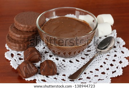 Bowl of chocolate and sweets on wooden background
