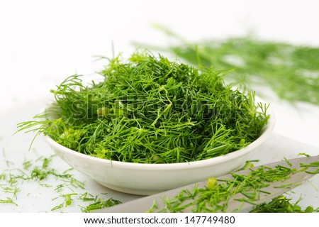 bowl of chopped fresh dill with sharp knife