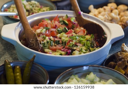 Bowl of classic Israeli salad.It is a chopped salad of finely diced tomato and cucumber.It's the most well-known national dish of Israel. - stock photo