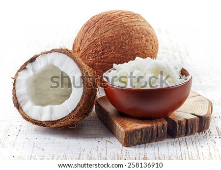 bowl of coconut oil and fresh coconuts on white wooden table - stock photo