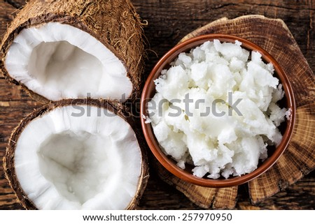 bowl of coconut oil and fresh coconuts, top view - stock photo
