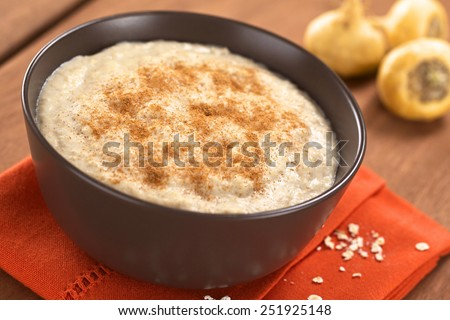 Bowl of cooked oatmeal porridge mixed with powdered maca or Peruvian ginseng (lat. Lepidium meyenii) with cinnamon on top and maca roots in back (Selective Focus, Focus in the middle of the porridge)  - stock photo