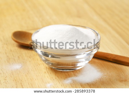 bowl of cooking soda and wooden spoon on table - stock photo