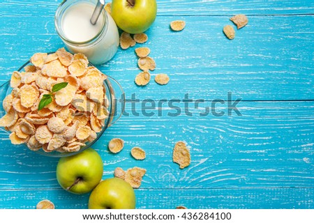 Bowl of cornflakes cereal on a blue wooden table and fresh apple, milk behind. Horizontal image with copy space. - stock photo