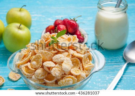 Bowl of cornflakes cereal on a blue wooden table and fresh strawberry, apple, milk behind.