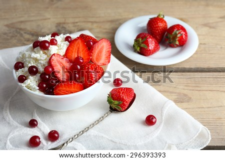 Bowl of cottage cheese with strawberry and cranberry on table, closeup
