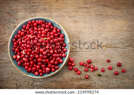 bowl of cowberries on old wooden table - stock photo