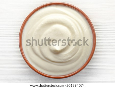 bowl of cream on white wooden table, top view - stock photo