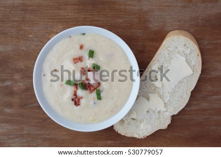 Bowl of creamy loaded potato soup with bacon bits and scallion on top.  Top down view.