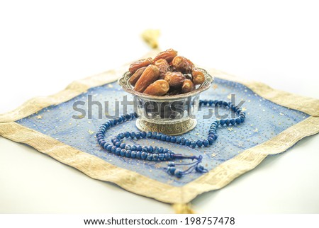 Bowl of dates and islamic rosary on decorative matt - stock photo