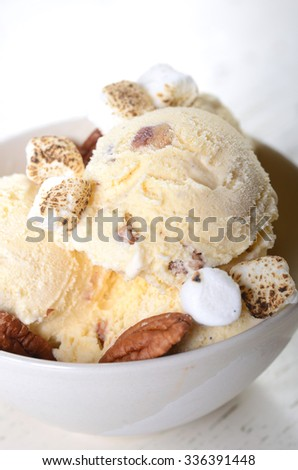 Bowl of delicious butter pecan ice cream with toasted pecans and marshmallows - stock photo