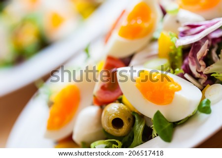Bowl of delicious fresh salad with mozzarella, eggs, olives and pepper