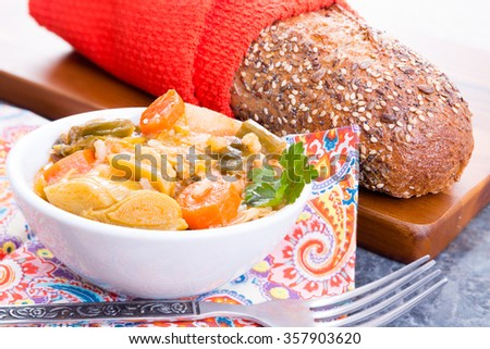 Bowl of delicious hot healthy Turkish leek soup served with a loaf of wholegrain bread with flax seeds for a tasty starter to a winter meal - stock photo