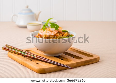 Bowl of delicious pad thai served with green tea. - stock photo