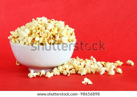 Bowl of Delicious Popcorn spilling onto a red background - stock photo
