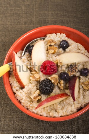 Bowl of delicious steel cut oats with fresh fruit, honey - stock photo