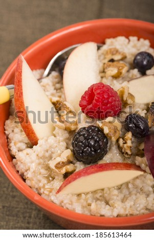Bowl of delicious steel cut oats with fresh fruit, nuts honey - stock photo