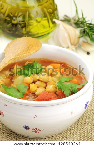 Bowl of delicious vegetarian homemade chickpea soup with carrots, celery stalks, chopped tomatoes and fresh parsley