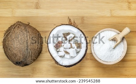 Bowl of desiccated coconut whole and chunks on wooden table background - stock photo