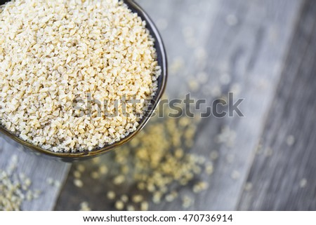 Bowl of dried bulgur wheat in rustic setting.