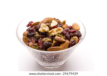 Bowl of dried fruits and nuts isolated on white with a drop shadow